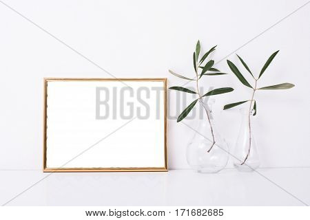 Golden frame mock-up on white wall background, home decor with flowers and objects