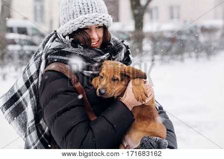 Stylish Hipster Woman Hugging And Smiling Cute Puppy In Snowy Cold Winter Park And Caressing. Moment