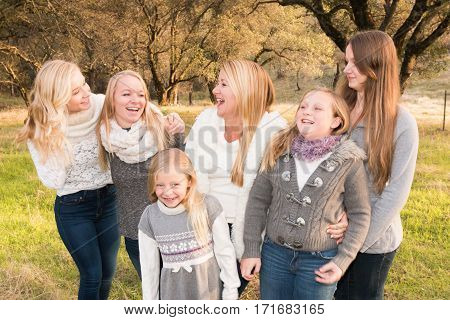 Beautiful Family of Girls Laughing Together Standing in Green Grassy Field