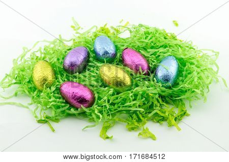 Easter Eggs on green shredded paper with yellow chickens