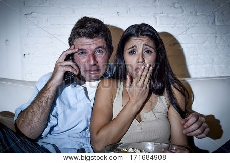 young couple at home sofa couch hug watching television movie together looking sad crying depressed with tv drama film in expressive face gesture