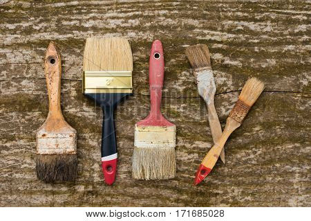 Set of old brush for coloring the walls Brush painting wooden furniture close up Paintbrush on wood background Vintage old painting brushes.