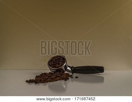 portafilter with delicate scattered grains of coffee on a white surface for barista