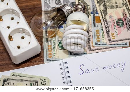 Energy saving concept. Electric light bulb with dollar bills pen and calculator