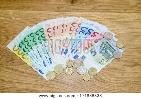 many different euro banknote and coins on wood background