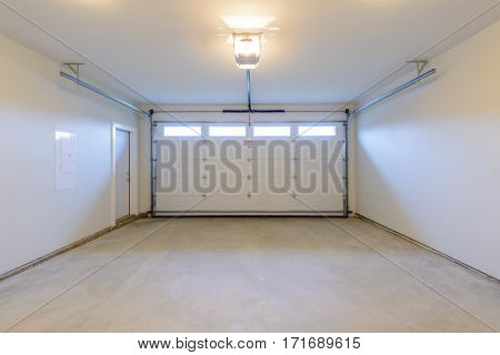 An empty garage with door and windows.