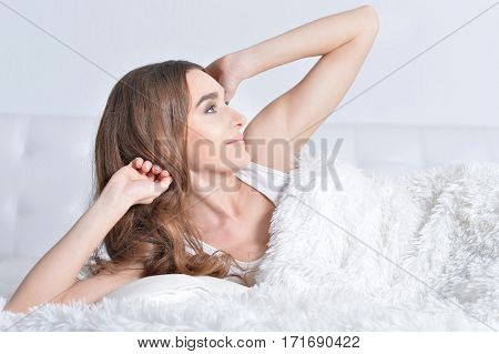 young beautiful woman relaxing at home in bed