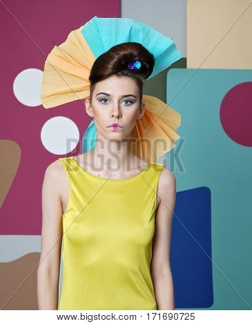 Eccentric outfit: yellow dress with open shoulders, headdress made of paper, mouth closed. Color background: simple geometric forms