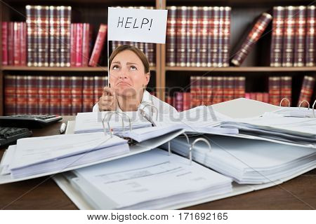 Young Unhappy Female Accountant Holding Help Flag With Pile Of Folders On Desk