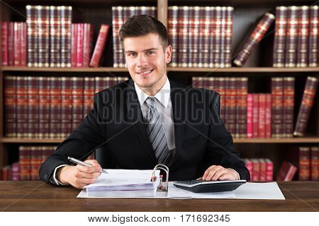 Portrait Of A Young Male Accountant Calculating Financial Document