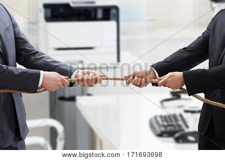 Close-up Of A Two Businesspeople Hand Playing Tug Of War In Office