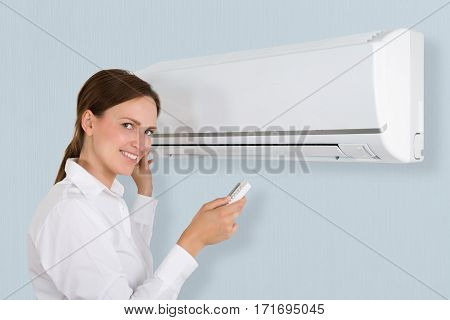 Portrait Of A Happy Businesswoman Using Air Conditioner In Office