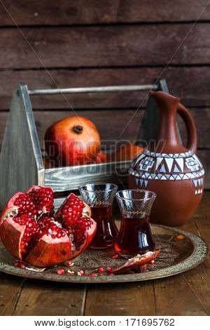 juicy pomegranate - whole and cut, top view. With jug. Juicy pomegranates on wood