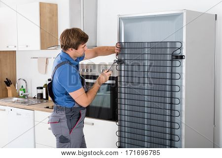 Serviceman In Overall Working On Fridge With Screwdriver In Kitchen