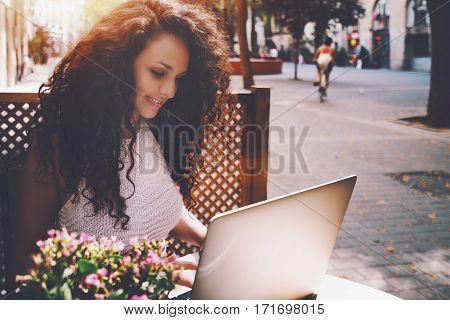 Attractive beautiful white caucasian brunette freelancer girl with curly black hair is sitting in street cafe in front of wooden fence and working on her modern laptop on sunny day