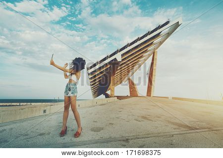 Woman is shooting selfie on touch pad in front of huge solar panel curly girl is making photo of herself with digital tablet camera in front of modern photovoltaic power station