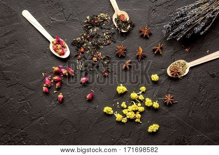 Herbs on spoons black stone background top view