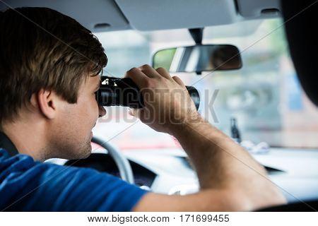 Private Detective Looking Through Binoculars Sitting Inside Car