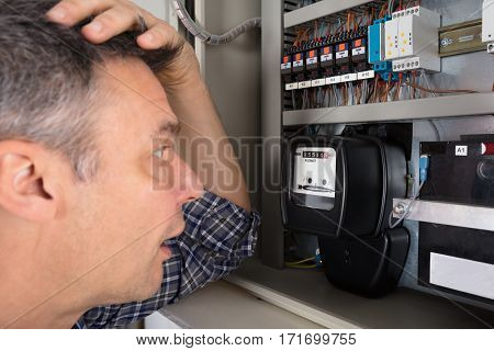 Close-up Of A Shocked Man Looking At Electricity Meter