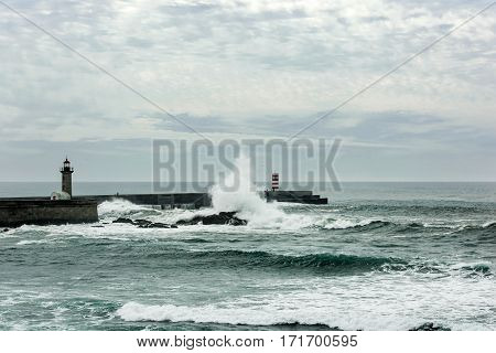 stormy sea waves crushed over pier with lighthouse in Porto Portugal