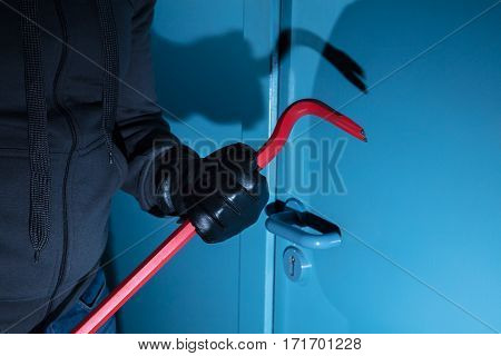 Close-up Of A Burglar Hand Holding A Crowbar Outside The Door