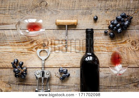 Glasses of red wine and bottle on wooden table background top view