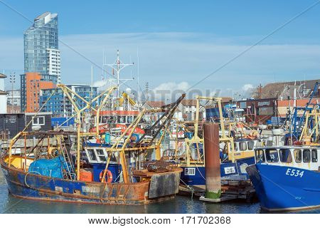 Portsmouth, UK. 16th February 2017. Fishing boats and sailing vessels are moored up at The Camber in Old Portsmouth against the backdrop of the Gunwharf Quays leisure facility.