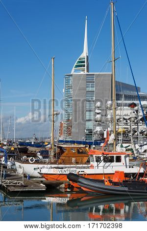 Portsmouth, UK. 16th February 2017. Fishing boats and sailing vessels are moored up at The Camber in Old Portsmouth against the backdrop of the Landrover/BAR racing sailing headquarters. .