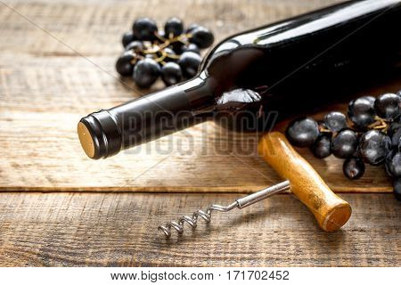 Red wine set with bottle and fresh grape on wooden desk background