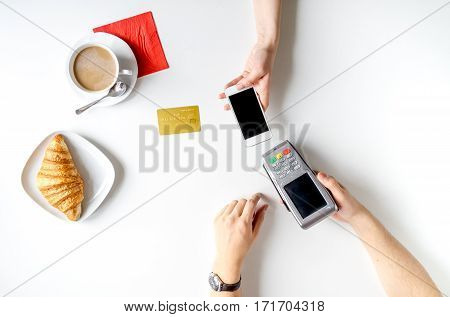 Business breakfast with coffee, croissant and credit card payment on white desk background top view