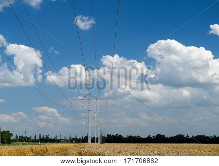 A Transmission Line On A Background Of Wheat Fields And Sky With Clouds