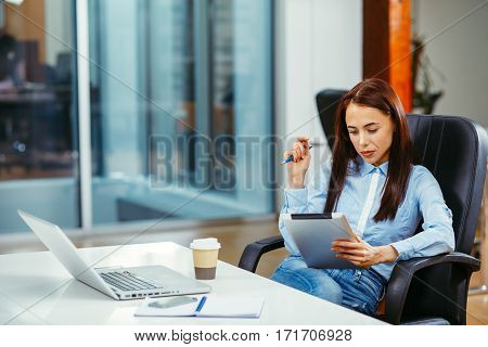 Young businesswoman working with a digital tablet with laptop on the table in front of her