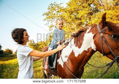 Little girl riding on a horseback with her mother walking nearby.