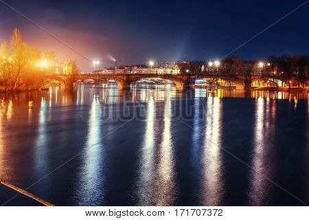 Scenic view of bridges on the Vltava river and of the historical center of Prague: buildings and landmarks of old town with red rooftops.