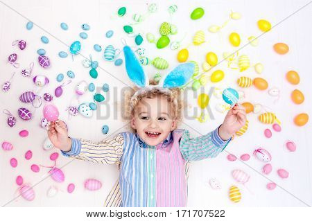 Child On Easter Egg Hunt. Pastel Rainbow Eggs.