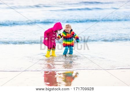Boy and girl running and jumping in the waves on North Sea beach during winter vacation in Holland. Kids play in ocean sand dunes on cold autumn or spring day. Beach fun for family with children.
