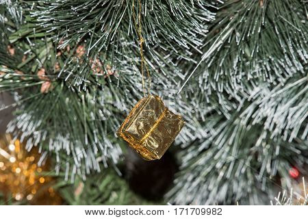 Present for the New Year's branch. Golden Christmas decorations. Close-up. Gift box on Christmas tree lights background