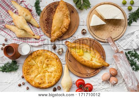 Traditional Georgian adjara khachapuri and Kolkh khachapuri on the table. Homemade baking. Top view. Flat lay.