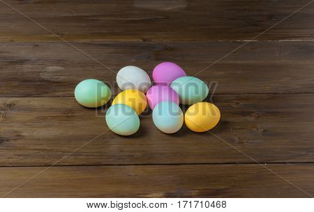 Colorful Easter eggs on vintage wooden table, rustic background, holiday concept