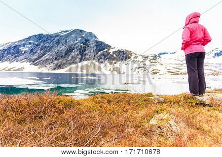 Tourism holidays and travel. Woman tourist standing near Djupvatnet lake relaxing meditation with serene mountains view Stranda More og Romsdal Norway Scandinavia.