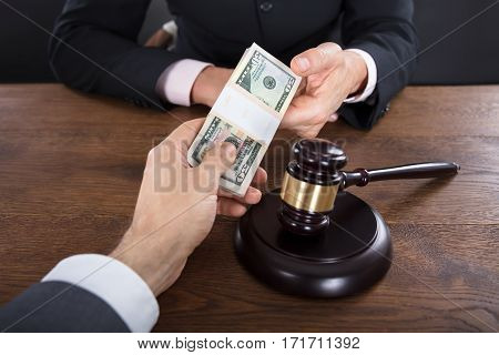 Close-up Of A Businessman Giving A Bribe To A Judge With Gavel On Wooden Desk
