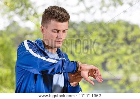 Fit young man checking time at park