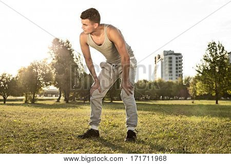 Full length of tired young man standing in park after jogging