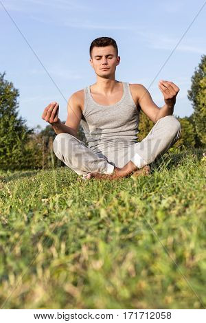 Young man meditating in park