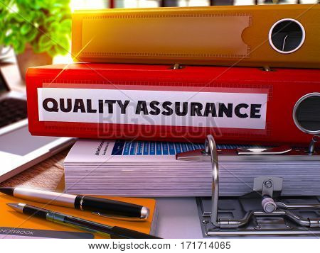 Red Ring Binder with Inscription Quality Assurance on Background of Working Table with Office Supplies and Laptop. Quality Assurance Business Concept on Blurred Background. 3D Render.