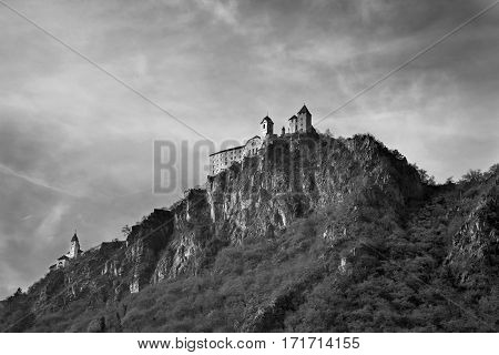 Italy- January 2017 Old castle on a cliff top a dangerous precipice rock forest beautiful white chapel rare treeswindows lockhigh castle on the hill black and white image