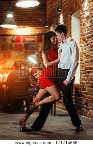 Dancing young couple on a white background. Passionate salsa