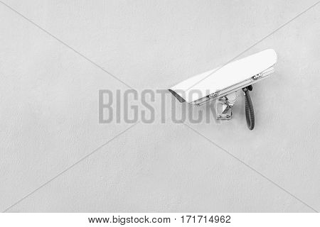white security camera on white wall closeup