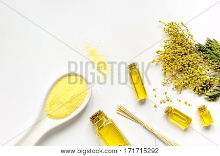 Yellow sea salt with essential oils cosmetic set on white background top view mock up