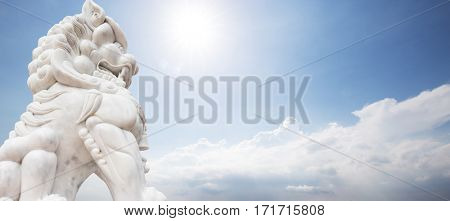 white stone lion sculpture in blue sunny sky